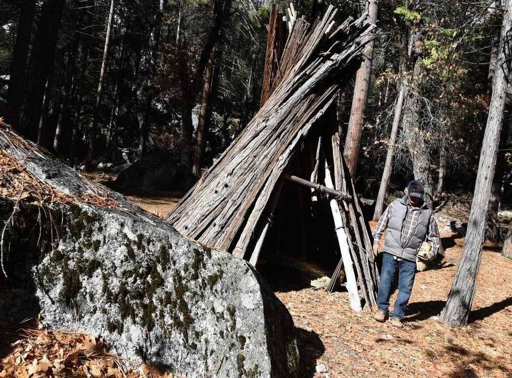 Tribal elder Bill Tucker walks past a reconstructed umacha, a Native American dwelling made of cedar bark, at the Wahhoga village under construction in Yosemite Valley, Nov. 30, 2017. Photo credit:JOHN WALKER