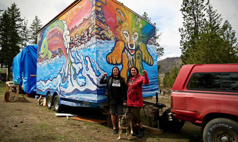 Mayuk (left) and Kanahus Manuel (right), founders of the Tiny House Warriors, in front of a completed tiny house on the Neskolinth Reserve outside of Kamloops, British Columbia. Photos by Janice Cantieri