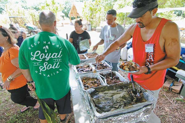 Makawao resident Joshua Faleulu (far right) and Joey Gonsalves, executive director of Hui No Ke Ola Pono, load up on the many dishes that were cooked in the imu during a workshop at the Maui Nui Botanical Gardens over the weekend. The Maui News / COLLEEN UECHI photo lutheran indian ministries native news