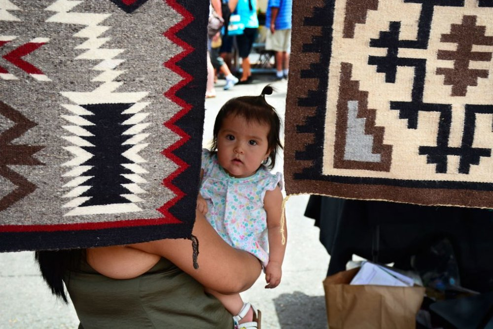 A Navajo mother and weaver holds her Native American daughter in her booth at the Santa Fe Indian Market in Santa Fe, New Mexico. Photo credit: Getty/Robert Alexander