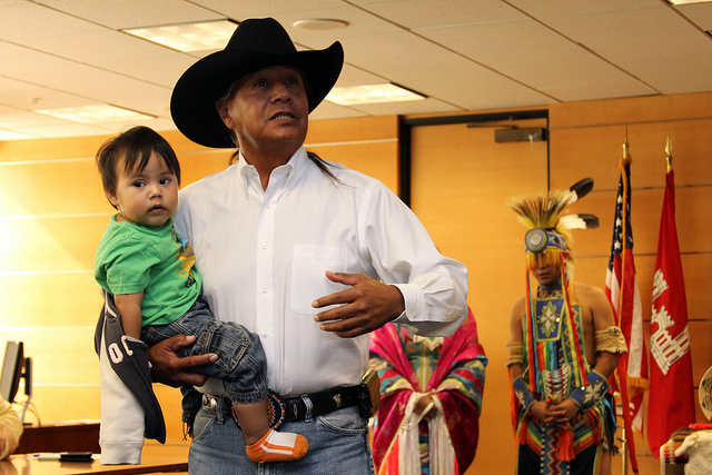 Photo of a Seminole man holding his child at an American Indian Heritage Month celebration. Photo by Los Angeles District, Flickr CC