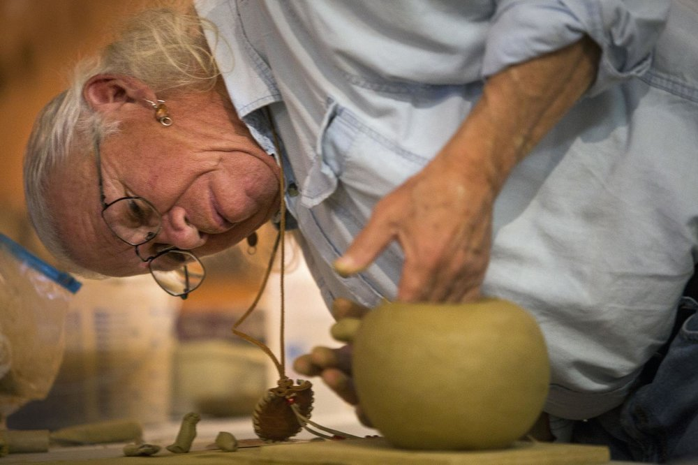 """""""In 1976 I made my first pottery in a class when I got out of the army."""" Keith Brown also known as """"Little Bear"""" carefully smoothes out a clay pot in the making during a Native American Arts festival at the Native American Studies Center on Dec. 1, 2018 in Lancaster. Andrew Whitaker/Staff  By Andrew Whitaker awhitaker@postandcourier.com lutheran indian ministries native news"""