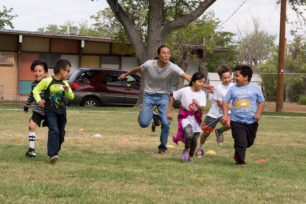 Elementary school students from the Native American Community Academy in Albuquerque, N.M., play running games with Dustin Martin (center) as part of after-school activities. Wings of America is a New Mexico-based group that educates young Native Americans about their cultural and spiritual connection to running. Photo credit: Story Hinckley/The Christian Science Monitor