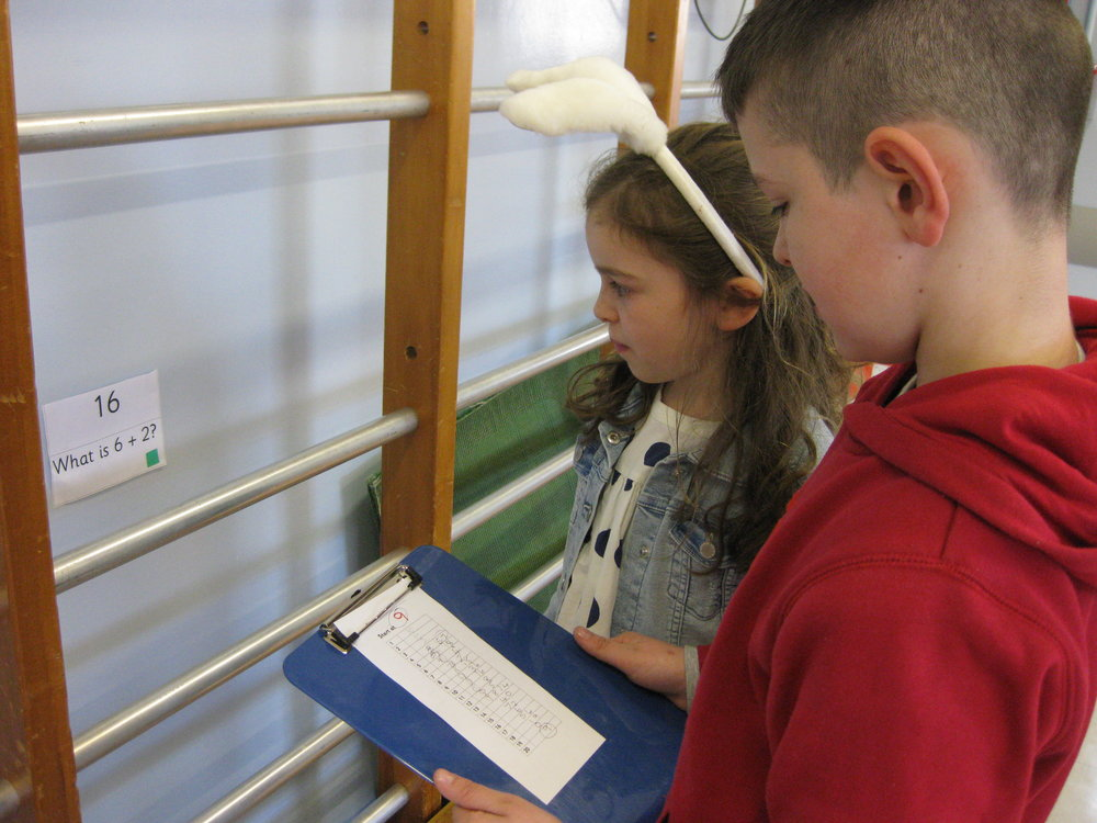 Emma and Alfie work together on the Maths Hunt