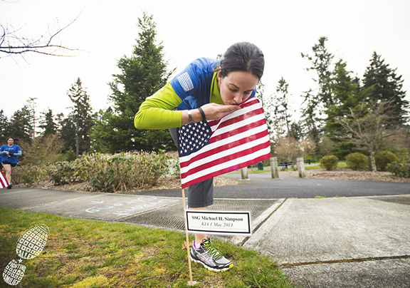 Photo by Ingrid Barrentine of Grit City Photography. Krista Simpson pausing at her husband's flag at her local wear blue chapter Saturday run.