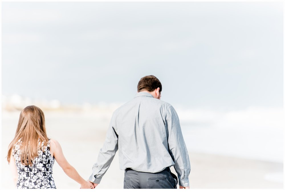 engaged couple holding hands on beach