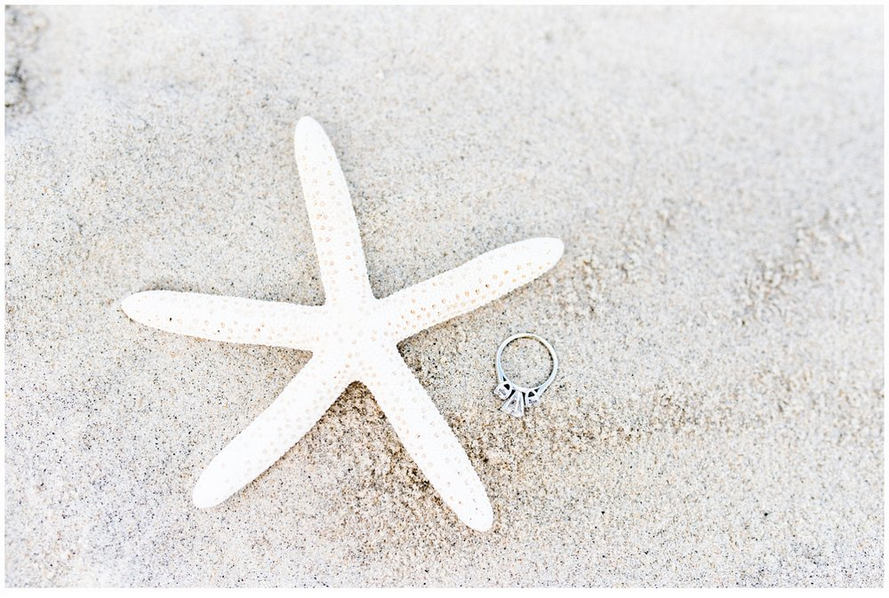 starfish in sand with engagement ring
