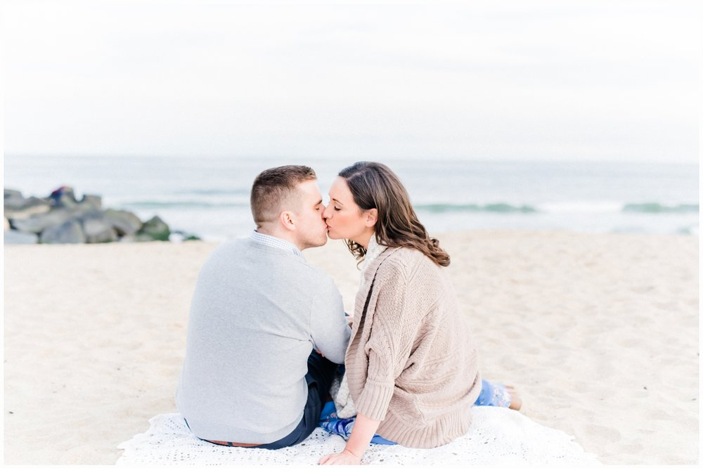 engaged couple on beach kissing