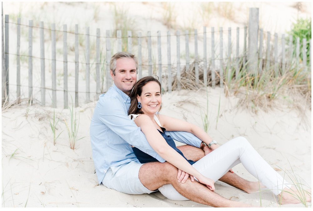 couple sitting on beach dunes