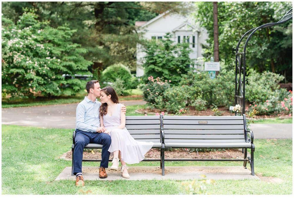 couple engaged sitting on a park bench