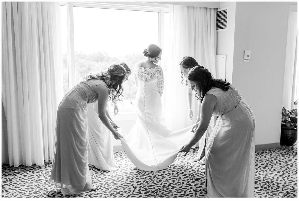 bridesmaids fixing brides dress