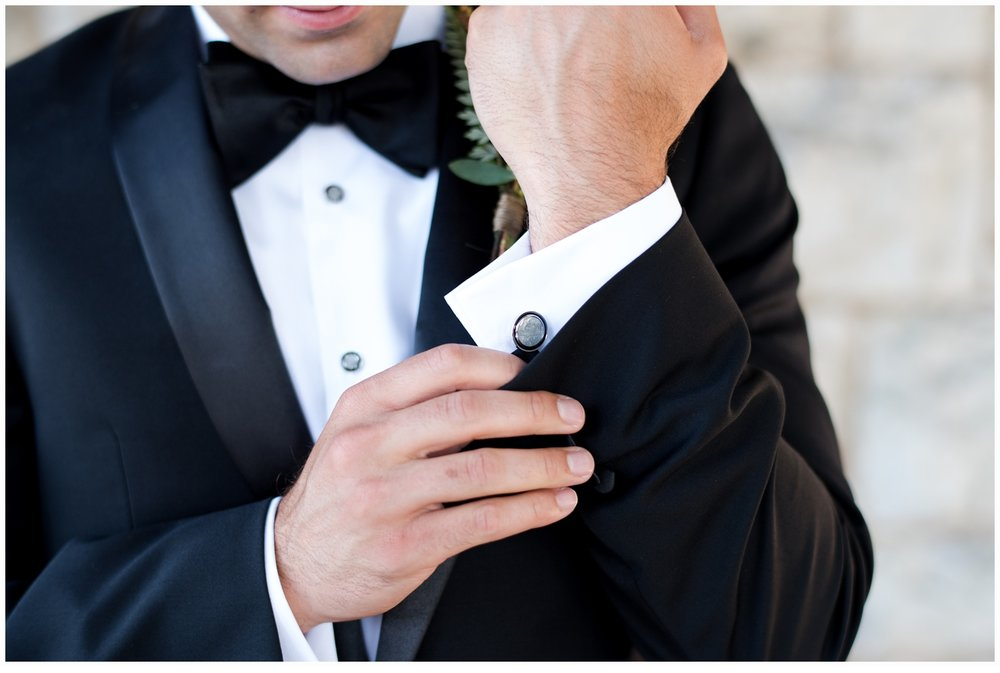 groom putting his cuff links on shirt