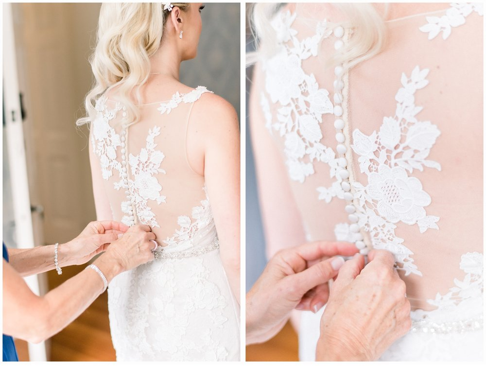 mom helping bride into wedding gown