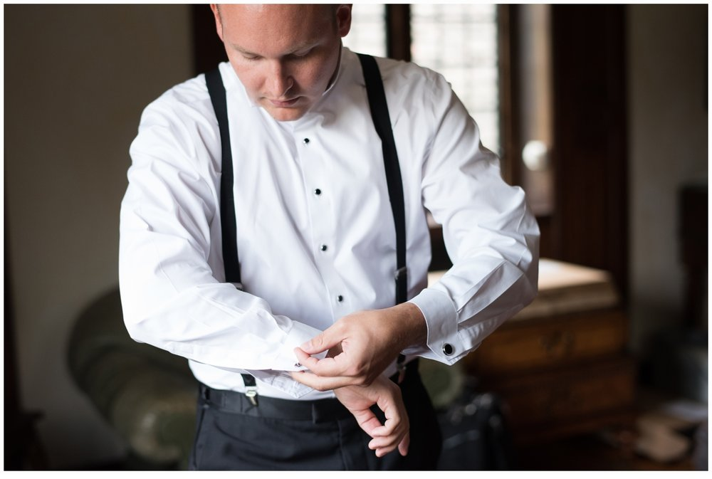 groom putting on cufflinks on wedding day