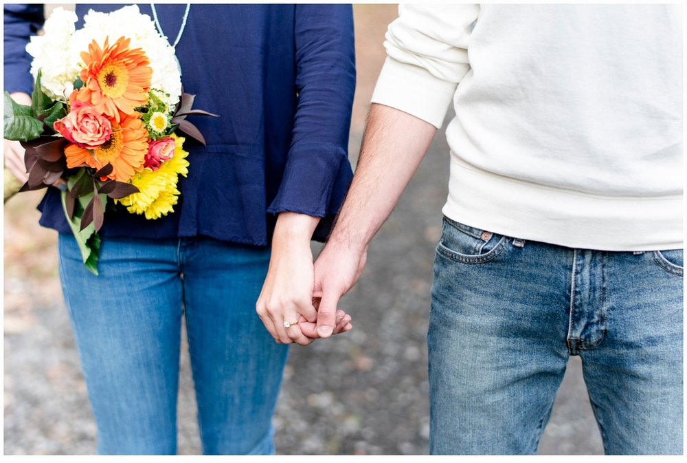 couple holding hands with bouquet on an engagement session