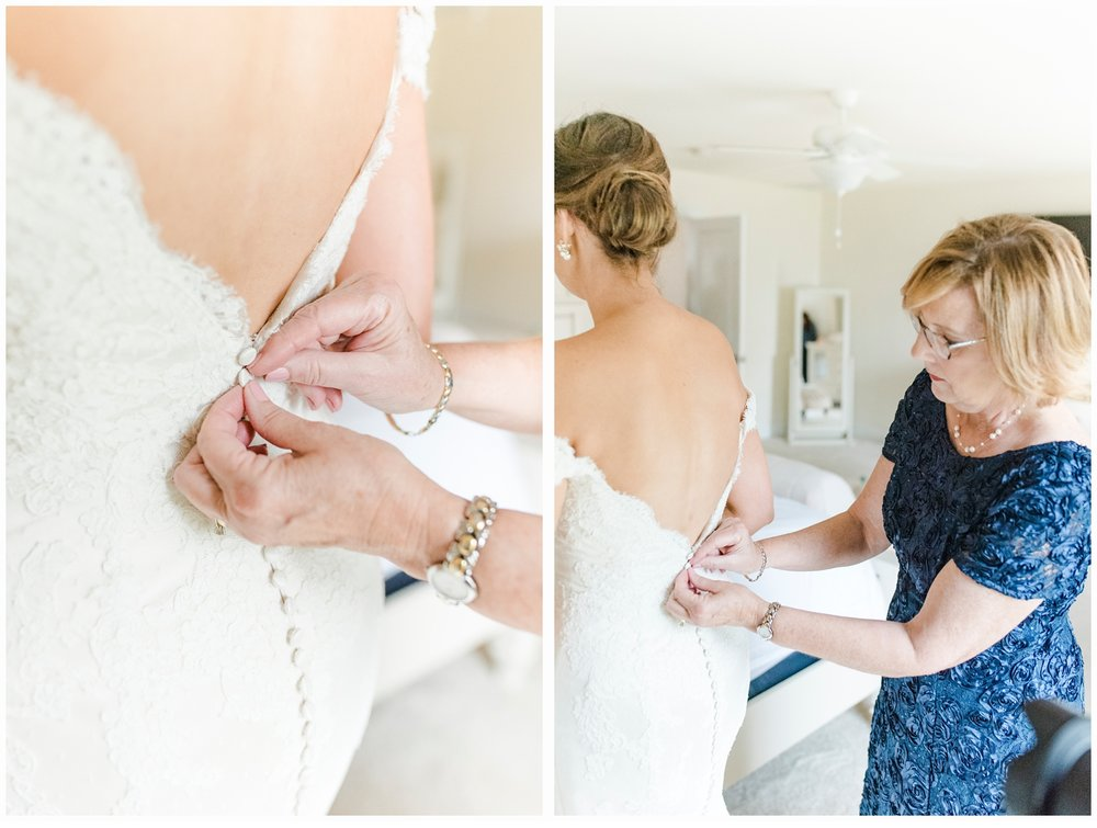 mom zipping up daughter's wedding dress