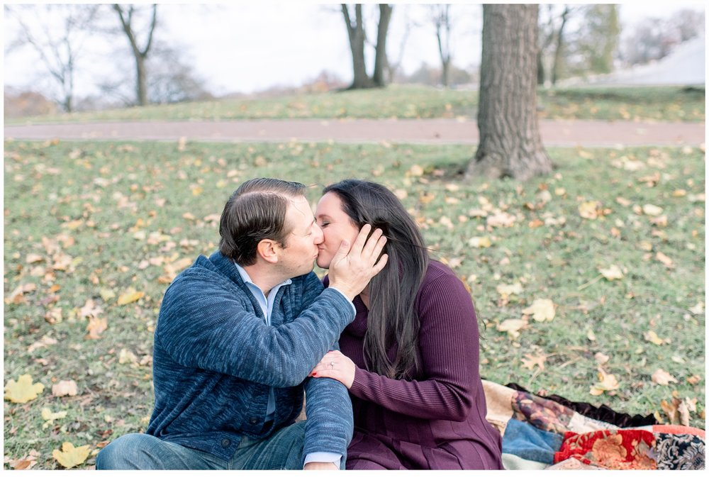 engaged couple kissing on lawn