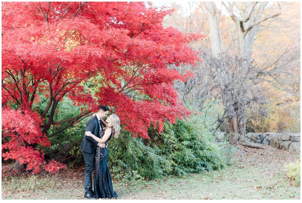 couple in front of a pretty red tree