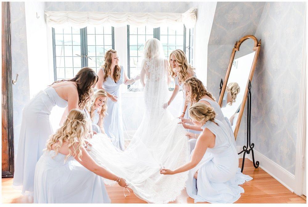 bridesmaids helping bride put on wedding gown