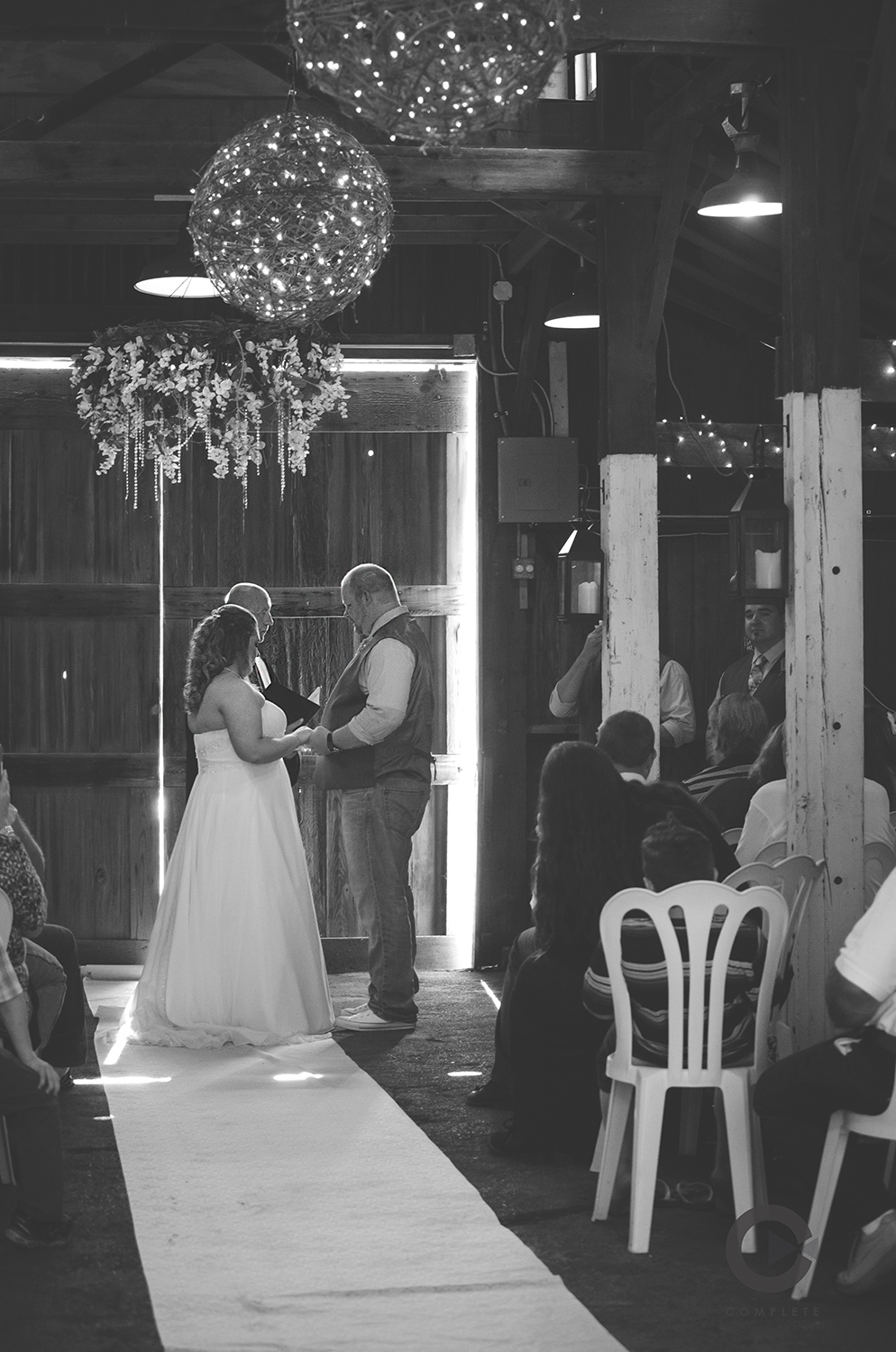 Inside the barn, a chandelier hung above them as they said I Do.