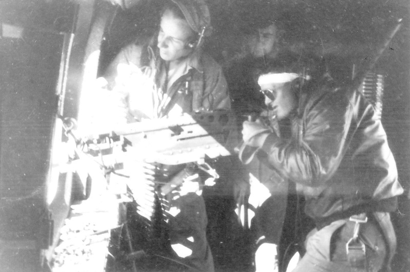 Waist gunner position, persons unknown. There appears to be a third face in the picture, suggesting a training mission.