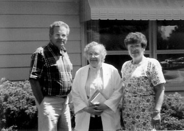 Don and Lois Greenlee flanking Marian Garrett In front of 1143 Crestmore Way, Mason City, Iowa, undated photo