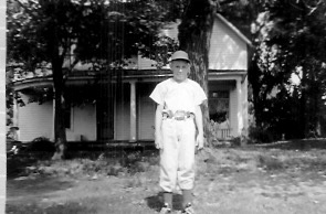 Craig in Little League uniform in front of Rental at 322 South Lincoln, Colfax, Iowa