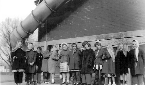 Second Grade girls, Winter 1954-1955 standing on concrete wall of sandbox. Note the metal fire escape tube. L-R: Martha Monroe, Sherry Faidley, Sharon Mallory, Beth Barrett, Terri Smith, Ann Cashman, Marilyn Brown, Carolyn Zachary, Kathleen Hunter, Cathy Webb, Kay Purcell, Linda Stewart
