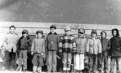 Second Grade boys, winter 1954-1955, standing on sidewall of cement sandbox. L-R: Bill Muck, Gary Beals, Doug Thomas, Vernon Seieroe, Don Evans, Robert Van Elsen, Dennis Conn, Dick Ward, Craig Garrett. I was wearing a bright red parka.