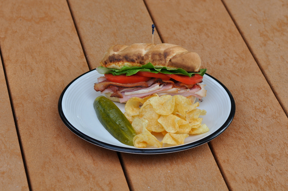 Club Sub made with fresh sliced Boars Head meat and cheese, romain lettuce, juicy tomatoes, served with chips and fresh sliced pickle!