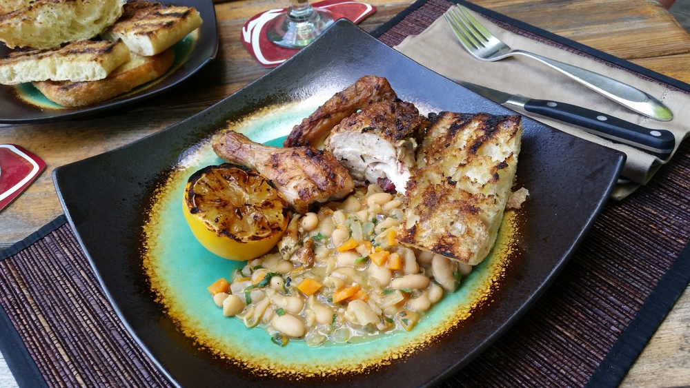 Grilled Tuscan Style Chicken, cooked over white beans and carrots, with fresh grilled lemon halves and grilled ciabatta bread rubbed with fresh garlic.