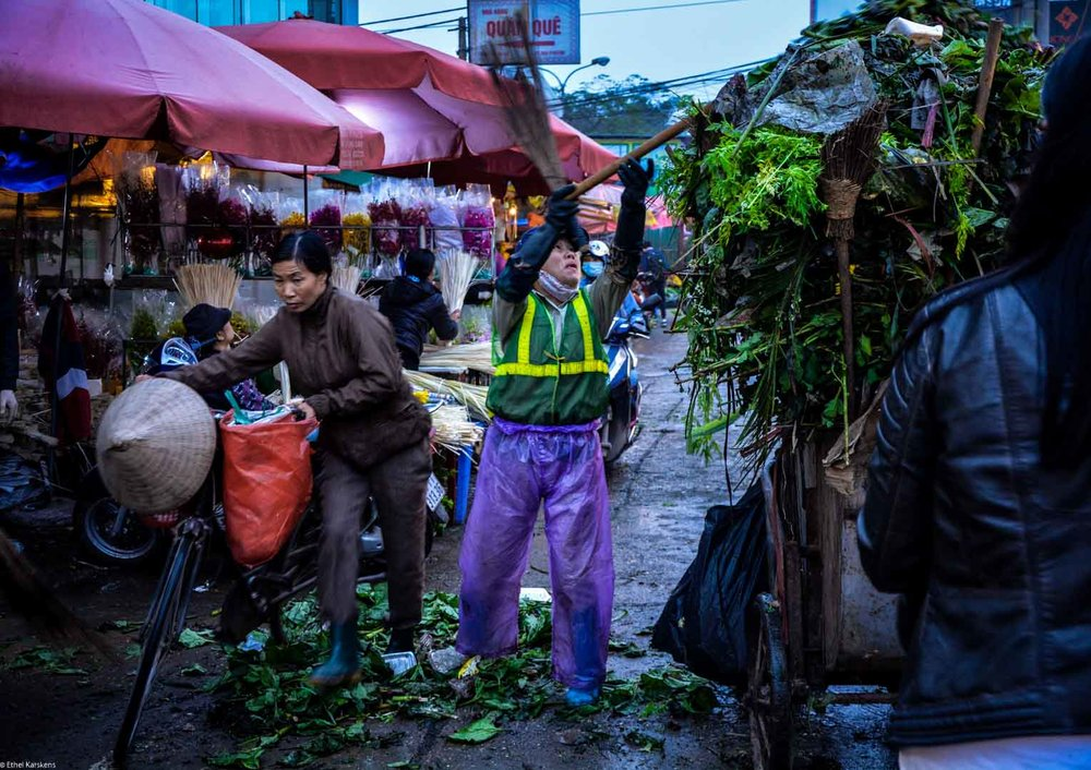 Woman cleaning the the flower market