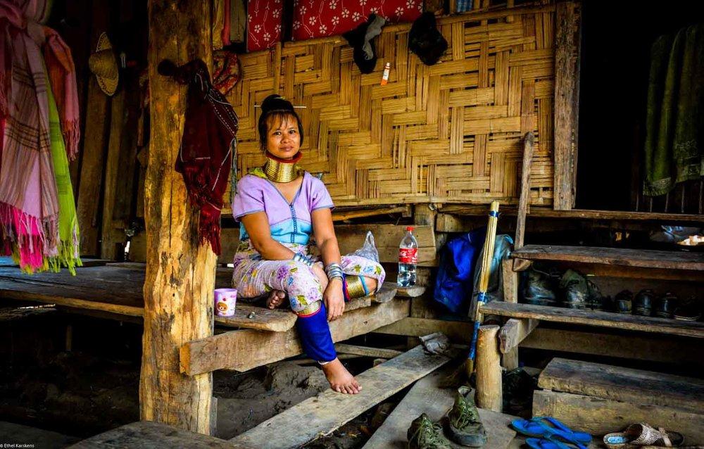 Femme assise devant sa maison