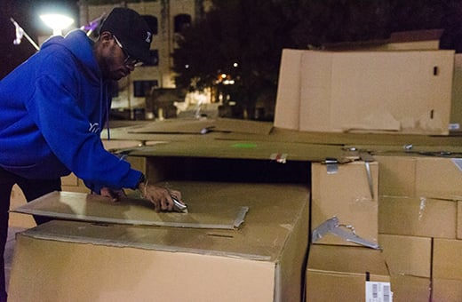 Wilson Meeks, 5th-year architecture student, puts the finishing touches on Phi Beta Sigma's massive cardboard box structure erected in Bosco Plaza during Sleep Out for the Homeless Thursday night. The members of the fraternity spent the night in the structure to raise awareness for the homeless and those below the poverty line in Manhattan and Riley County.