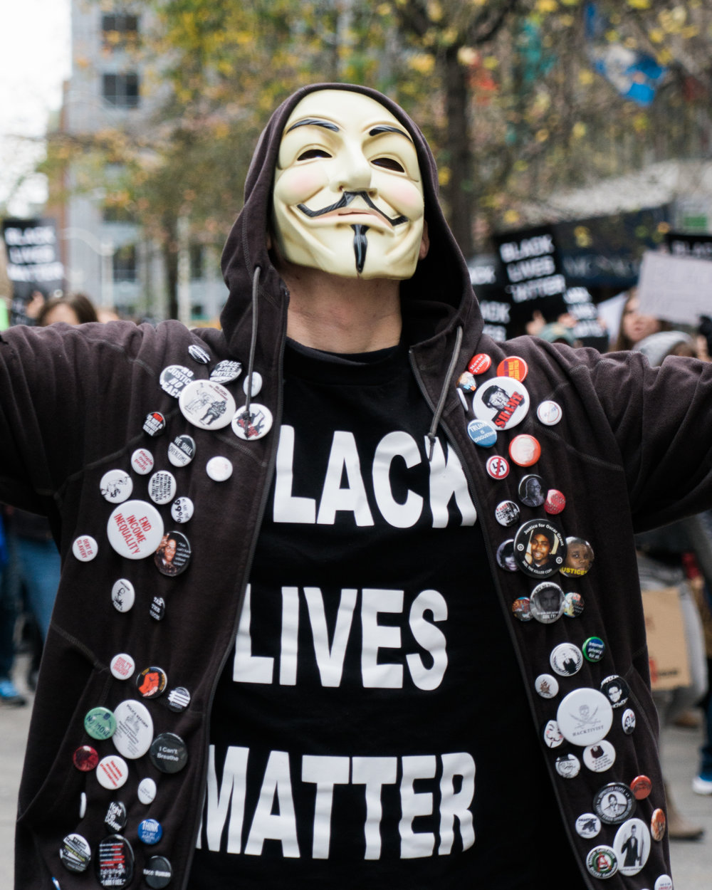 "A man sports an ubiquitous Guy Fawkes mask and dozens of buttons with slogans displaying messages like ""Fight the Power"" and ""Trump is disgusting""."