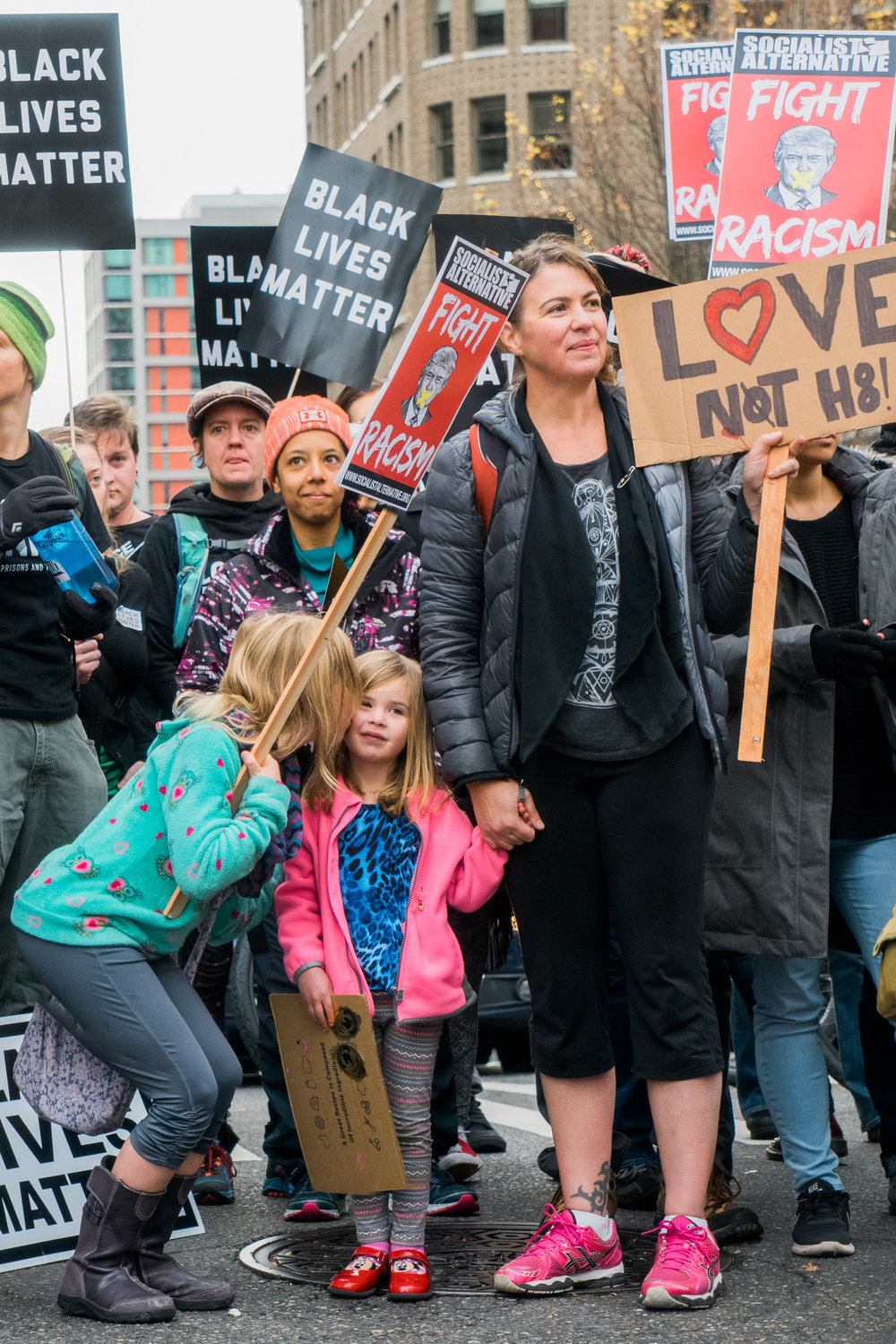 "A young girl gives her little sister a kiss on the cheek during a pause in the protest as mother displays a cardboard sign reading ""Love not H8!"""