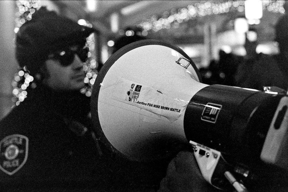 Justice for Mike Brown Seattle is taped to a protesters bullhorn. Black Lives Matter Protest, November 2015. Photography by Anthony Allison
