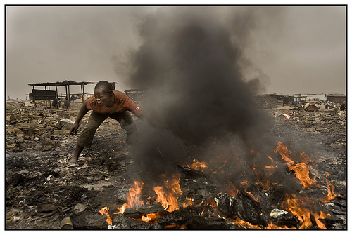 A boy holds his breath while burning a pile of discarded electronics in Ghana