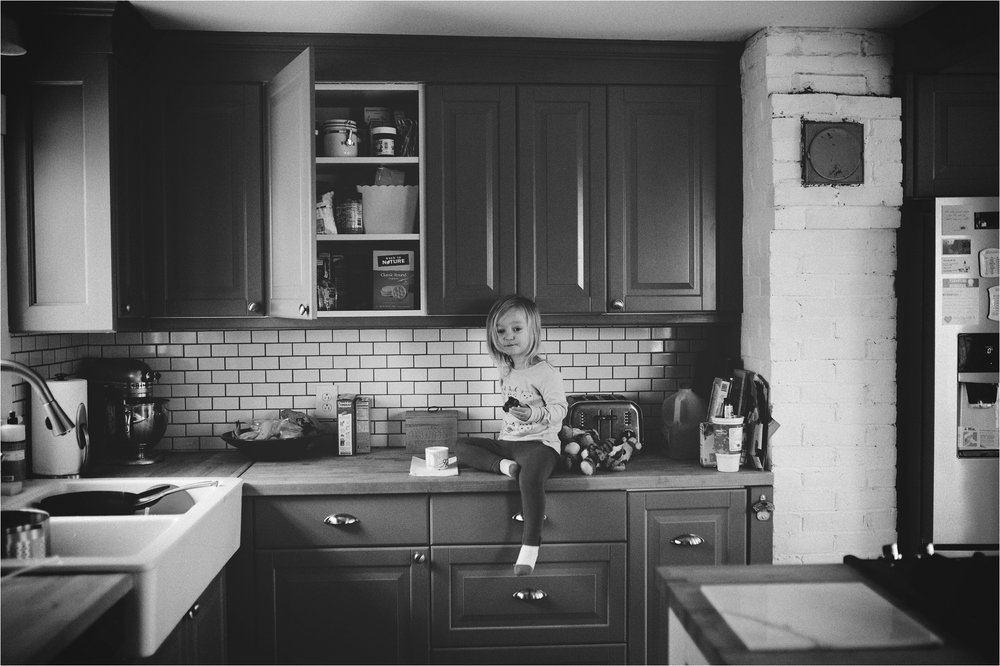 little girl sitting on the kitchen counter