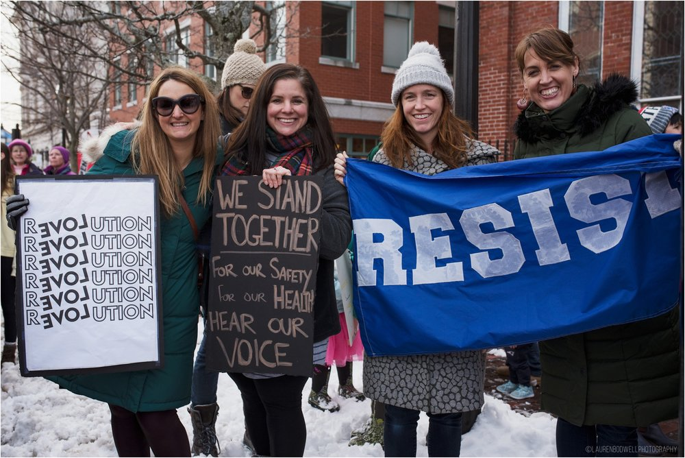 four women holding signs