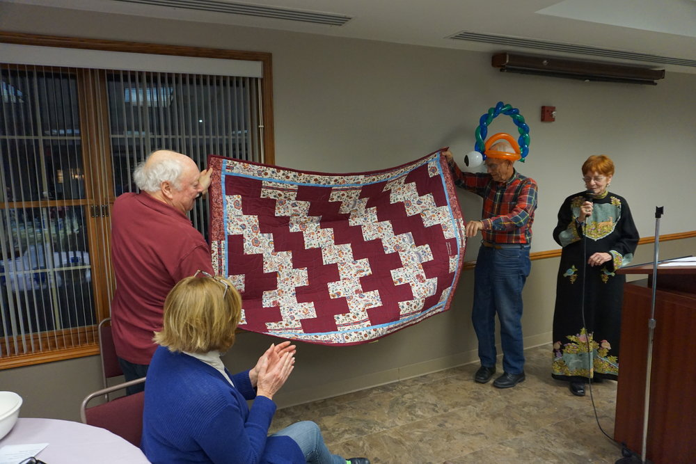 Leadership team member Bill Meers reveals the beautiful quilt door prize created by Museum board member, Charlotte Paugh.