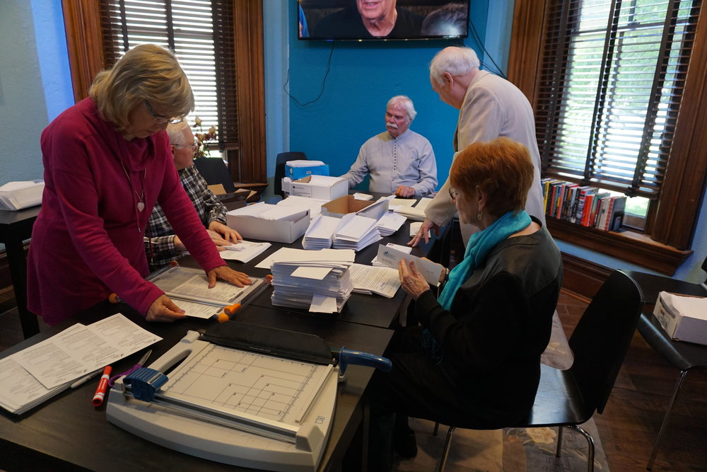 Members of the leadership team stuff envelopes, fold letters and prepare nearly a thousand appeal for donations letters to go out in support of the museum's efforts to create peace in Dayton and the world.