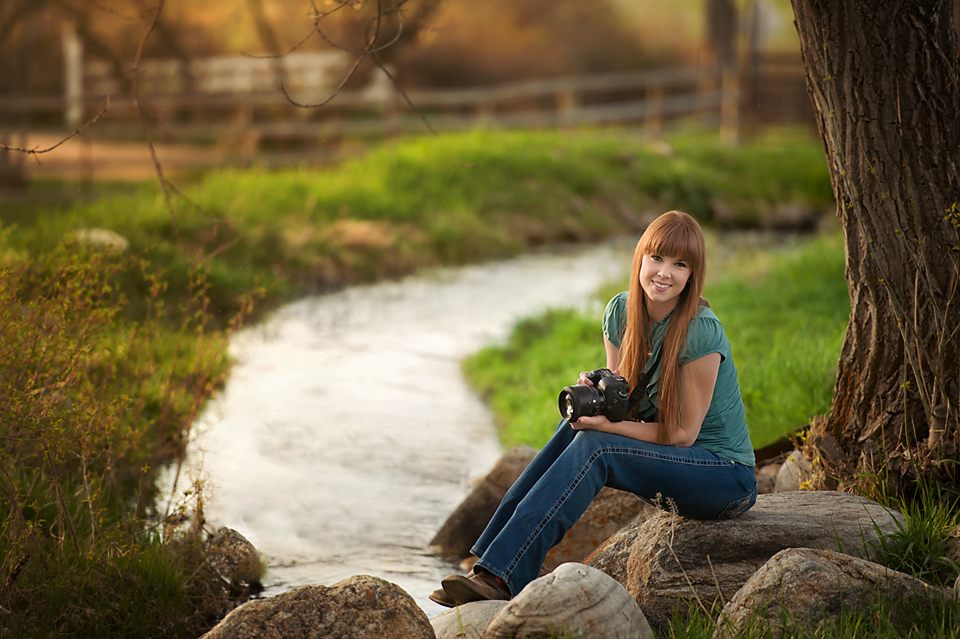 woman by stream with camera