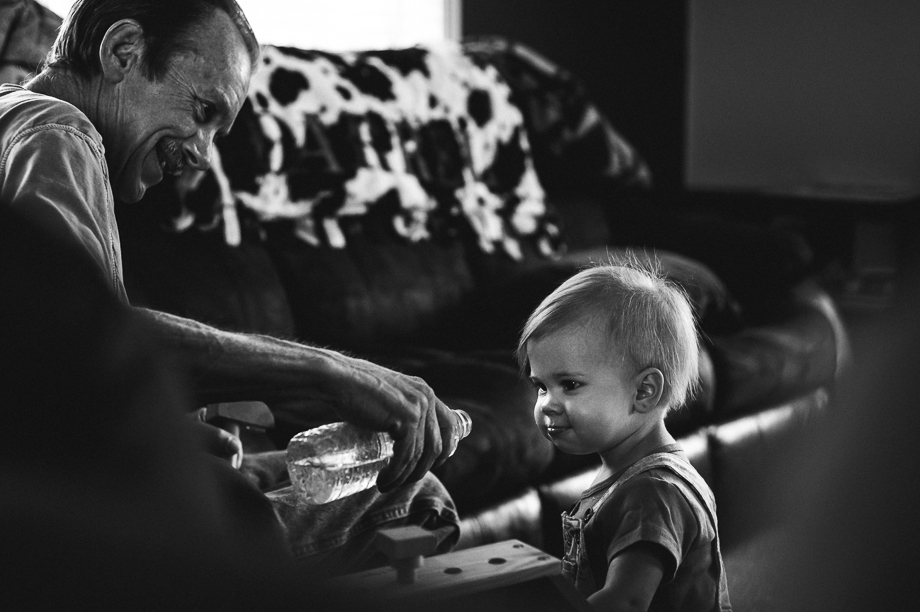 grandpa and granddaughter playing with water bottle
