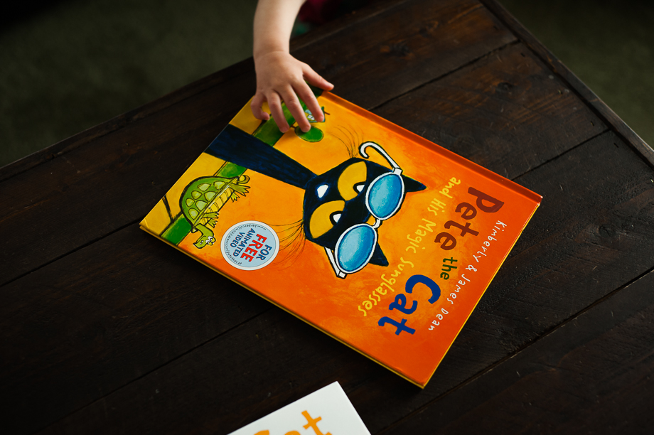 child's hand reaching for Pete the Cat book