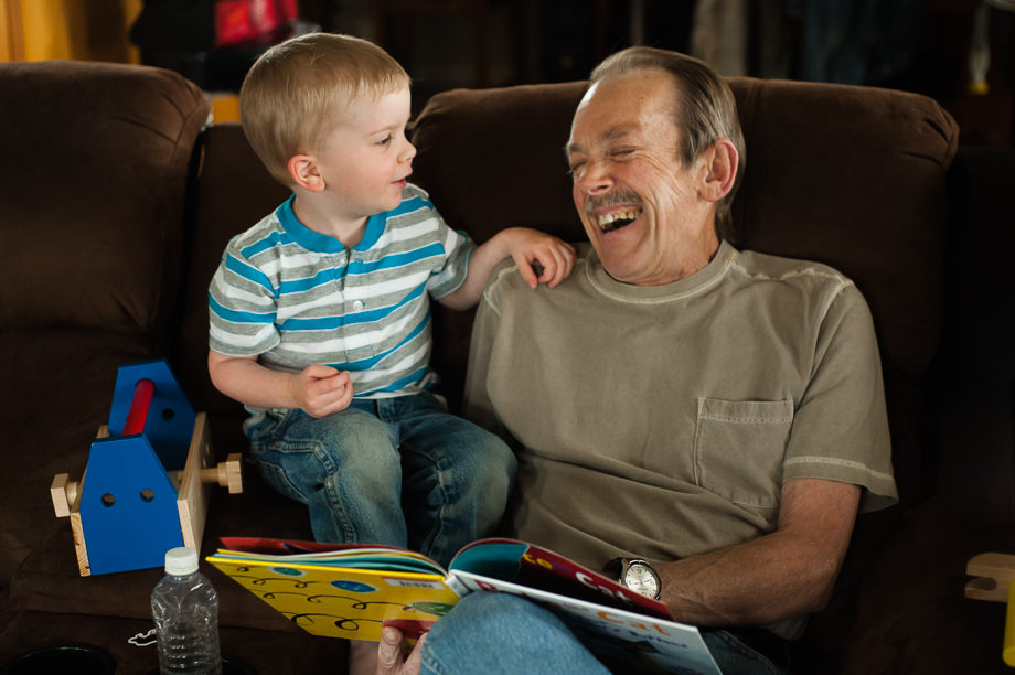 man and boy laughing over book