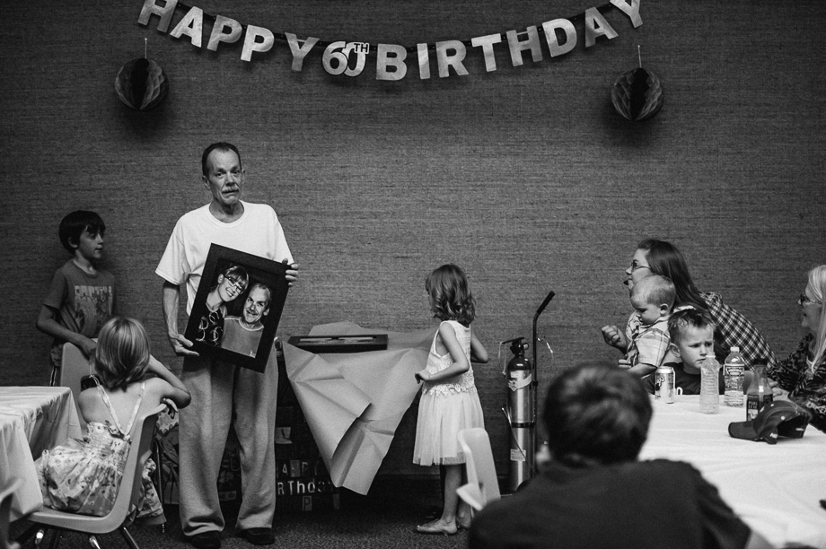 emotional dad holding photo at birthday party