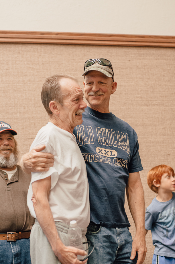 smiling older men friends embrace