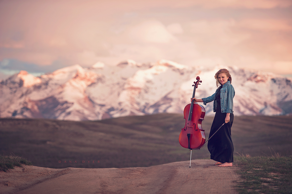 Girl with cello in front of mountain