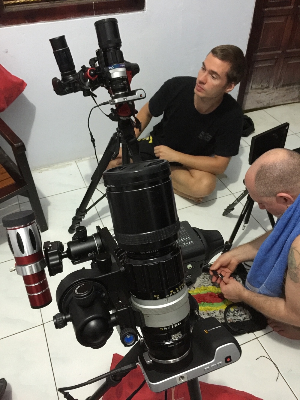 "Andrais and James are seen here preparing the two identical cameras systems in preparation for transporting to our two island locations. Here you can see the identical BlackMagic Design Pocket Cinema Cameras equipped with 300mm Nikor lens. Camera system ONE (seen here in the foreground) also has the 20x iPhone add-on lens. The iPhone is not attached as I was using it to take this picture. One of the drawbacks of using your iPhone (or any other ""smart phone"") to photograph the eclipse is that you will not be able to use your smart phone for all the other photos you'll be wanting to take. Both systems are supported by the SkyWatcher Star Adventurer Tracking Mount which is our mount of choice for the Eclipse Across America project."